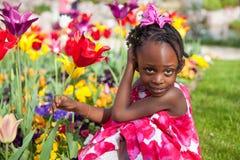 Nettes kleines Mädchen, das im Garten spielt Stockfoto