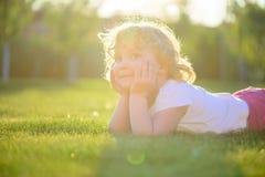 Nettes kleines Mädchen, das im grünen Gras liegt Stockbilder