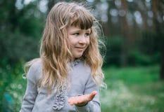 Nettes kleines Mädchen, das im grünen Park spielt Stockbild