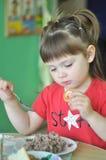 Nettes kleines Mädchen, das im Kindergarten, Schule isst Vorschule, die Brei für das Mittagessen isst Kind, Babynahrung, Lebensmi Stockfotos