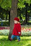 Nettes kleines Mädchen, das im roten Mantel ankleidet lizenzfreie stockbilder