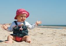 Nettes kleines Mädchen, das im Sand sitzt Stockbild