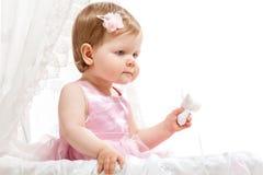 Nettes kleines Mädchen, das im Schätzchenbuggy sitzt lizenzfreie stockfotografie