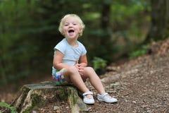 Nettes kleines Mädchen, das im Wald spielt Stockfotografie