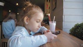 Nettes kleines Mädchen, das am intelligenten Telefon am Café verwendet Glückliches Kind, das den Spaß und Entspannung nach der Sc stock video