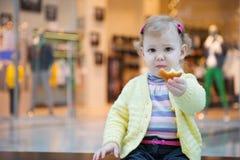 Nettes kleines Mädchen, das Kekskuchen auf Bank isst Lizenzfreie Stockfotos