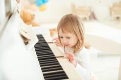 Nettes kleines Mädchen, das Klavier im hellen Raum spielt Stockfotos
