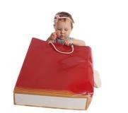 Nettes kleines Mädchen, das Korne in Papierbeutel setzt Stockfoto