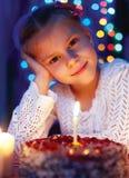 Nettes kleines Mädchen, das Kuchen mit einer Kerze betrachtet Lizenzfreies Stockbild