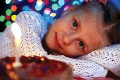 Nettes kleines Mädchen, das Kuchen mit einer Kerze betrachtet. Stockbild