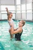 Nettes kleines Mädchen, das lernt, mit Trainer zu schwimmen Lizenzfreie Stockfotos