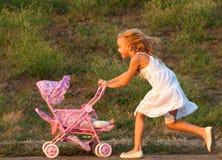 Nettes kleines Mädchen, das mit ihrem Schätzchenspielzeug spielt Lizenzfreies Stockbild