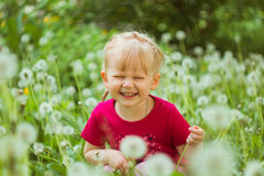 Nettes kleines Mädchen, das mit Löwenzahn lächelt Lizenzfreie Stockfotografie