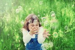 Nettes kleines Mädchen, das mit Seifenblasen auf dem grünen Rasen im Freien, glückliches Kindheitskonzept, Kind hat Spaß spielt Stockfotos