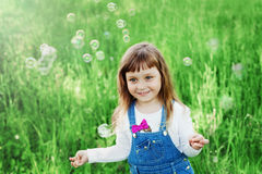 Nettes kleines Mädchen, das mit Seifenblasen auf dem grünen Rasen im Freien, glückliches Kindheitskonzept, Kind hat Spaß spielt Lizenzfreie Stockfotografie