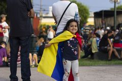 Nettes kleines Mädchen, das mit venezolanischer Flagge am Protest spielt stockbilder