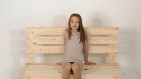 Nettes kleines Mädchen, das in Mode auf einem Bank Studio sitzt und für die Kamera aufwirft stock video