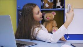 Nettes kleines Mädchen, das modernes Smartphone verwendet lizenzfreie stockfotografie