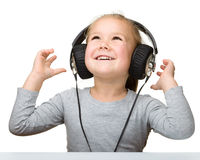 Nettes kleines Mädchen, das Musik unter Verwendung der Kopfhörer genießt Lizenzfreies Stockfoto