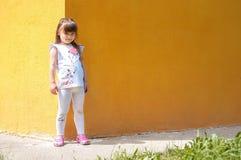 Nettes kleines Mädchen, das nahe der gelben Wand steht Lizenzfreie Stockbilder