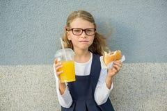 Nettes kleines Mädchen, das Orangensaft des Hamburgers hält Lizenzfreie Stockfotos