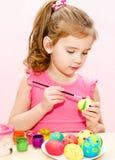 Nettes kleines Mädchen, das Ostereier malt Stockbild
