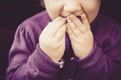 Nettes kleines Mädchen, das süße macarons mit dem schmutzigen Finger isst Stockfotografie