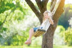 Nettes kleines Mädchen, das Spaß auf einem Schwingen in blühendem altem Apfelbaumgarten draußen am sonnigen Frühlingstag hat stockfotos