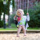 Nettes kleines Mädchen, das am Spielplatz schwingt Lizenzfreies Stockfoto