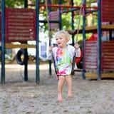 Nettes kleines Mädchen, das am Spielplatz schwingt Stockfoto