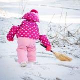 Nettes kleines Mädchen, das während des Tages des verschneiten Winters spielt lizenzfreie stockfotos