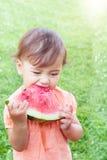 Nettes kleines Mädchen, das Wassermelone auf dem Gras in der Sommerzeit isst Lizenzfreie Stockfotos