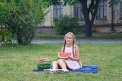 Nettes kleines Mädchen, das Wassermelone auf dem Gras in der Sommerzeit isst wenn dem langen Haar des Pferdeschwanzes und toothy  Stockfotos
