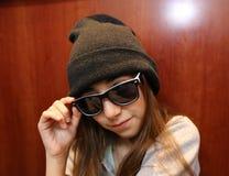Nettes kleines Mädchen, das weiße und schwarze Sonnenbrille tragend lächelt stockfotos