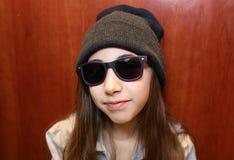 Nettes kleines Mädchen, das weiße und schwarze Sonnenbrille tragend lächelt stockfoto