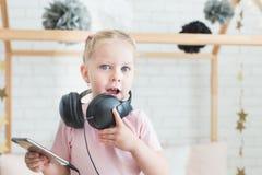 Nettes kleines Mädchen, das zu Hause Musik auf Kopfhörern hört lizenzfreie stockfotos