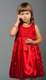 Nettes kleines Mädchen, das zum Telefon hört Stockfotografie