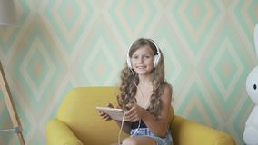 Nettes kleines Mädchen in den Kopfhörern hörend Musik unter Verwendung einer Tablette, Kamera und das Lächeln betrachtend stock video