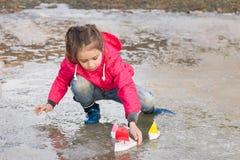 Nettes kleines Mädchen in den Regenstiefeln, die im Frühjahr mit dem bunten Nebenfluss der Schiffe steht im Wasser spielen Stockfotografie