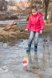 Nettes kleines Mädchen in den Regenstiefeln, die im Frühjahr mit dem handgemachten bunten Nebenfluss der Schiffe steht im Wasser  Lizenzfreie Stockbilder