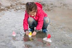 Nettes kleines Mädchen in den Regenstiefeln, die mit Schiffen wässern spielen im Frühjahr, Pfütze Stockbilder