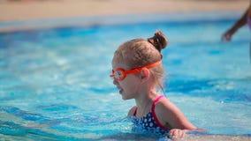 Nettes kleines Mädchen in den Schutzbrillen schwimmend im Swimmingpool stock video