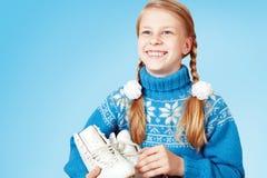 Nettes kleines Mädchen in der blauen warmen Strickjacke, die Zahl Rochen hält Stockfotos
