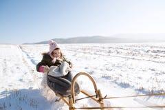 Nettes kleines Mädchen draußen in der Winternatur, sitzend auf Schlitten Lizenzfreie Stockbilder