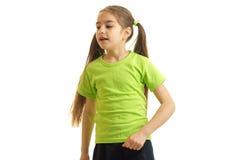 Nettes kleines Mädchen in einem grünen T-Shirt steht im Studio und blickt in Richtung Stockbild