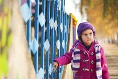 Nettes kleines Mädchen in einem Mantel mit Schal und in einem Hut, der zum Zaun anhält Stockfoto