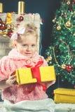 Nettes kleines Mädchen empfangen einen Geschenk nahen Verzierungsweihnachtsbaum stockbild