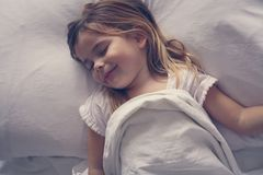 Nettes kleines Mädchen im Bett Stockfotografie