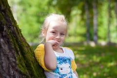 Nettes kleines Mädchen im gestrickten Bolero, der an einem Baum aufwirft Lizenzfreie Stockfotografie