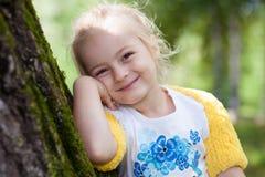 Nettes kleines Mädchen im gestrickten Bolero, der an einem Baum aufwirft Stockbild